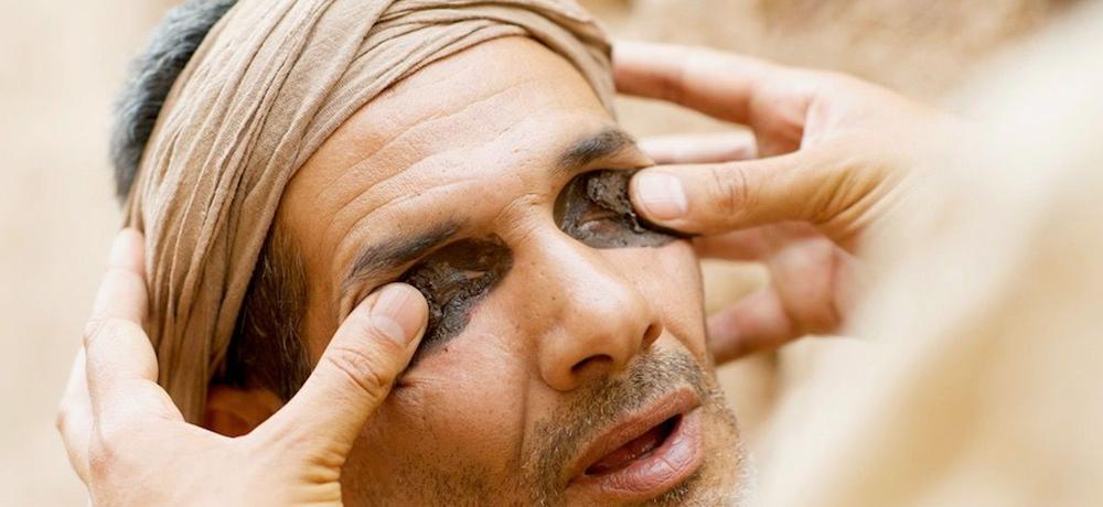 Jesus putting mud on the eyes of a blind man after Jesus spit