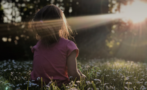 Girl in sunshine and field of daisies discovering her identity in Christ