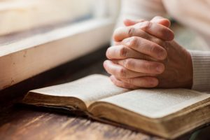 Praying hands with Bible, digging deeper into the Bible