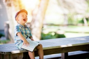 Child laughing with Bible, pray like a three year old