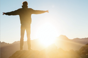 man on mountain looking at sunrise, being born again